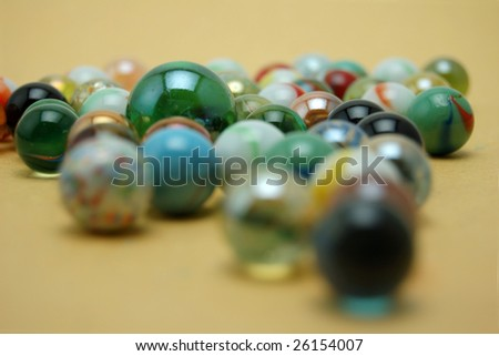 Colorful glass marbles amid one large marble - stock photo