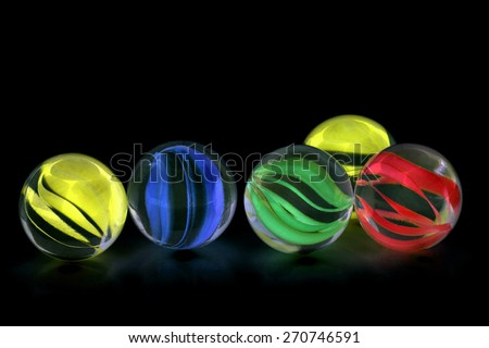 Colorful glass marbles isolated on black background - stock photo