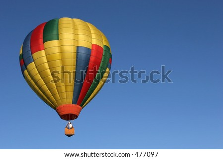 colorful golden hot air balloon in flight against a clear blue sky