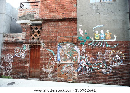 Colorful graffiti decorates the side of a dilapidated brick building. - stock photo