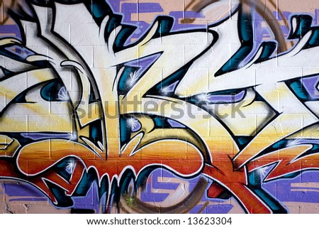Colorful graffiti spray painted on a brick wall.  Makes a great background or backdrop. - stock photo