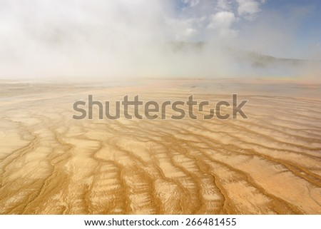 Colorful Grand Prismatic Spring with Steam and Morning Fog in Yellowstone National Park in Wyoming. - stock photo