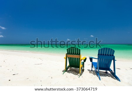 Colorful green and blue lounge chairs at tropical beach in Caribbean with beautiful turquoise ocean water, white sand and blue sky