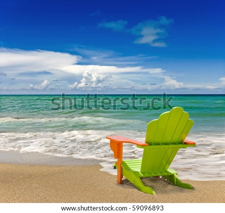 Colorful green and orange lounge chair at the tropical beach in Miami Florida with beautiful ocean waters and blue sky. - stock photo