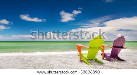 Colorful green and purple  lounge chair at the tropical beach in Miami Florida with beautiful ocean waters and blue sky. - stock photo