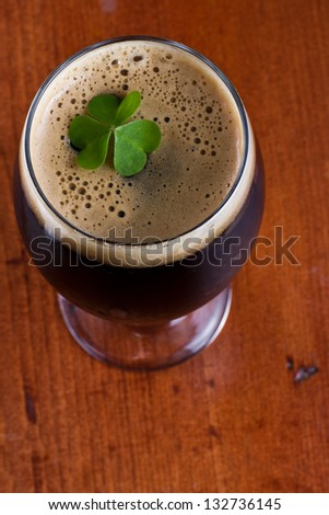 colorful green shamrock floating on top of an irish beer - stock photo