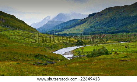 colorful green valley with river and some rain clouds in the back - stock photo