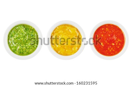 Colorful green, yellow and red spicy sauces in bowls isolated on white - stock photo