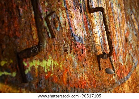Colorful grunge background of rusty iron surface with paint stains and hanged spoon - stock photo
