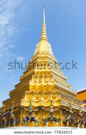 Colorful Guardian Statues Around the Base of a Shimmering Gold Chedi at the Grand Palace and Temple of the Emerald Buddha in Bangkok, Thailand - stock photo