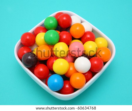 Colorful gumballs in white bowl on blue surface - stock photo