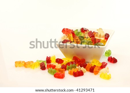 colorful gummy bears in a white bowl on a white background