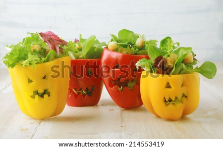 Colorful Halloween food background with colorful healthy stuffed red and yellow sweet bell peppers with cutout faces in the skin like Halloween jack-o-lanterns filled with green salad and cheese - stock photo