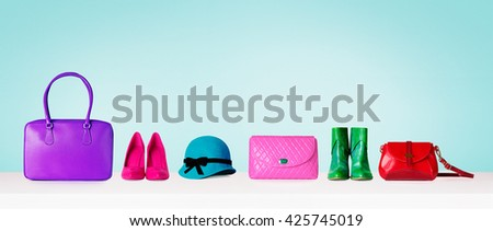 Colorful hand bags,shoes, and hat isolated on light blue background. Woman fashion accessories item. Shopping image.  - stock photo