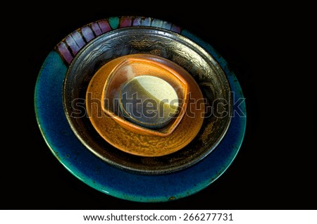 Colorful hand crafted ceramic pottery bowls saucer and serving dish stacked inside each other and isolated against black background - stock photo
