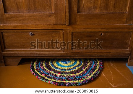 Colorful hand made knitted rug under a antique cabinet. Reuse of colorful flap. Folk nation creativity. Rustic style. Rough texture and bright design - stock photo