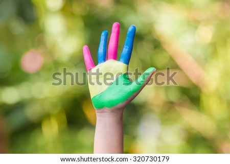 Colorful hand of the child  on green background - stock photo
