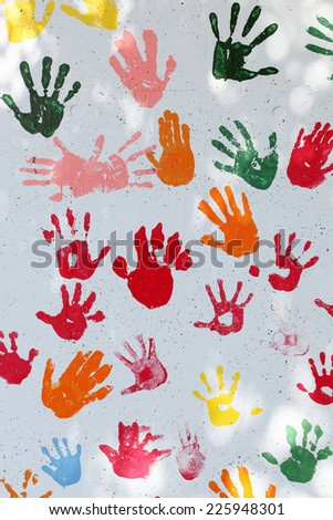 colorful hand prints on white wall background - stock photo
