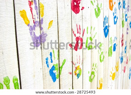 Colorful handprints on a while wooden wall from an angle - stock photo