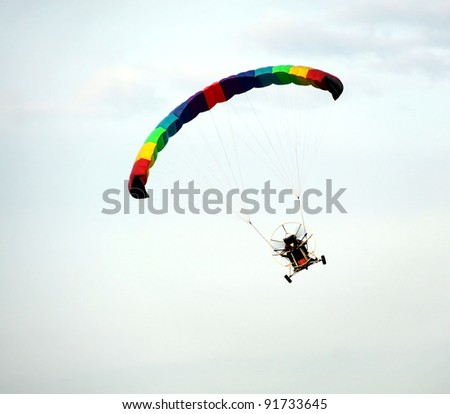Colorful hang glider in blue sky - stock photo