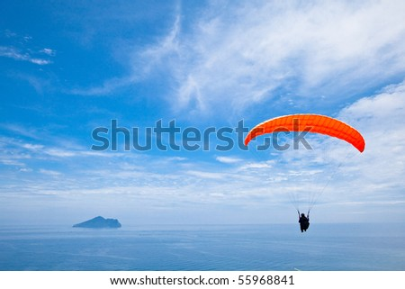 Colorful hang glider in blue sky over  sea - stock photo