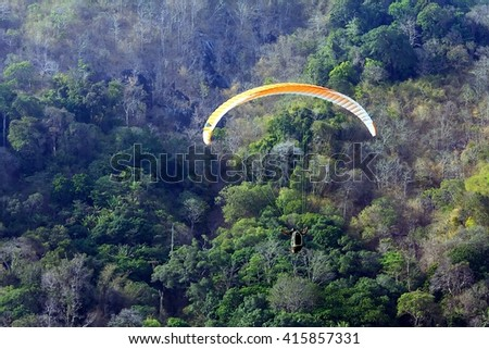 colorful hang glider in sky over blue sea at phuket thailand - stock photo