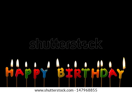 Colorful happy birthday candles on black background - stock photo