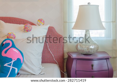 colorful hat in basket with pillows on kid's bed at home