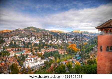 Colorful HDR image of the city of Granada, Spain from ancient Arabic fortress of Alhambra on a blue cloudy day - stock photo