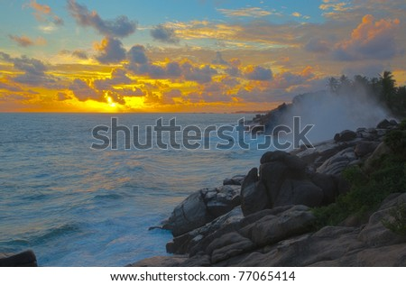 Colorful HDR Sunset with a break point in the background along the shoreline of Unawatuna South coast, Sri Lanka.