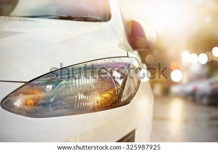 colorful headlights of white car after the rain at night on car parking - stock photo