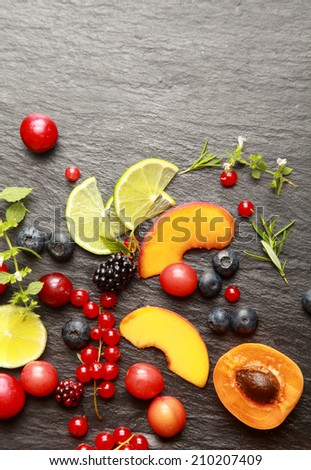 Colorful healthy sliced fresh fruit , assorted berries and herbs on a textured dark grey slate background with copyspace, view from above - stock photo