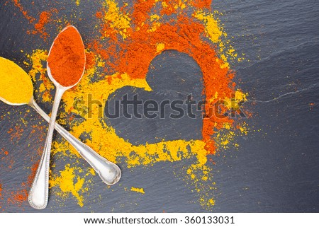 Colorful heart from spices on black background with two vintage spoons. Suggesting Valentines day concept. - stock photo