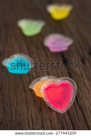 Colorful heart shaped jelly sweets with molds on old wood background - stock photo