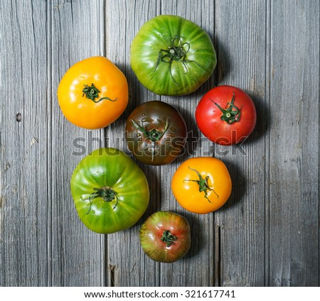 colorful heirloom tomatoes on wooden background - stock photo