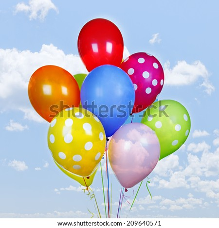 Colorful helium balloons on blue sky with clouds - stock photo