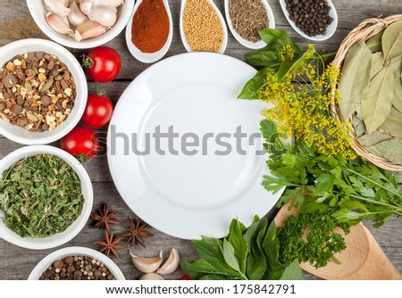 Colorful herbs and spices selection. Aromatic ingredients on wood table with empty plate for copyspace - stock photo