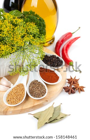 Colorful herbs and spices selection. Seasoning and aromatic ingredients on cutting board. Isolated on white background - stock photo