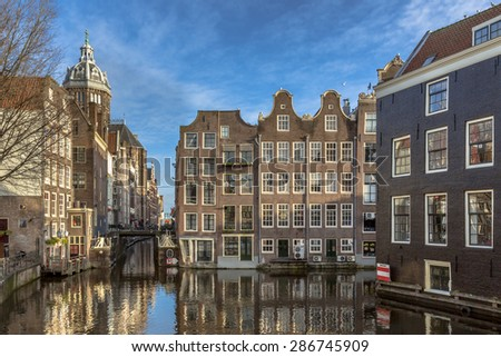 Colorful historic canal houses seen from the armbrug on a sunny day in Amsterdam - stock photo