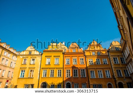 Colorful historical buildings facade in the Warsaw's old town on the morning sunlight. View from below with blue sky space - stock photo