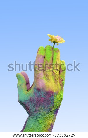 Colorful holi painted hand holding yellow flower