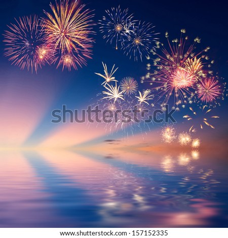 Colorful holiday fireworks in the evening sky reflection in water - stock photo