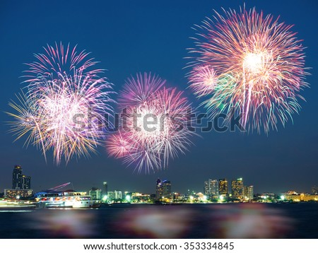 Colorful holiday fireworks in the night sky with boat floating on the sea and the city in background