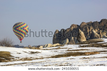 Colorful hot air ballon about to land the ground, Cappadocia - stock photo