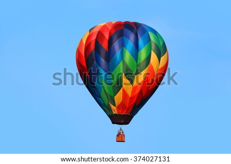 Colorful hot air balloon against blue background - stock photo
