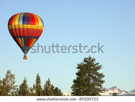 Colorful hot air balloon floating in the sky with the Oregon cascade mountains in the back ground.
