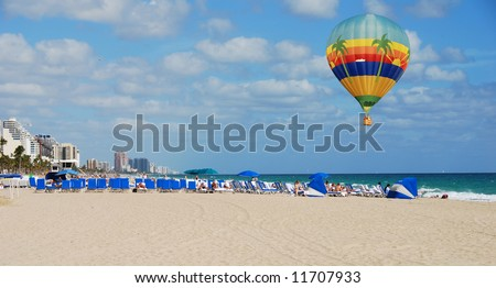 Colorful hot air balloon floating over the beach - stock photo