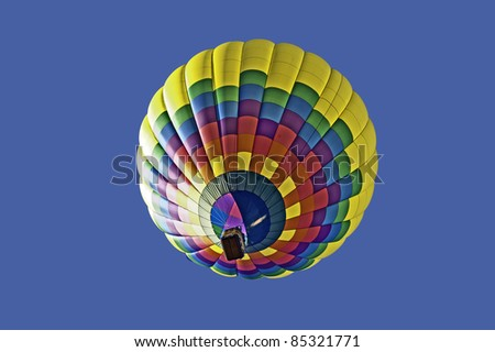 Colorful hot air balloon floats in a clear blue sky. - stock photo