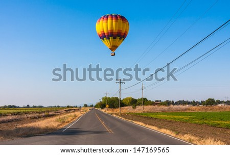 Colorful Hot Air Balloon flying above Road - stock photo
