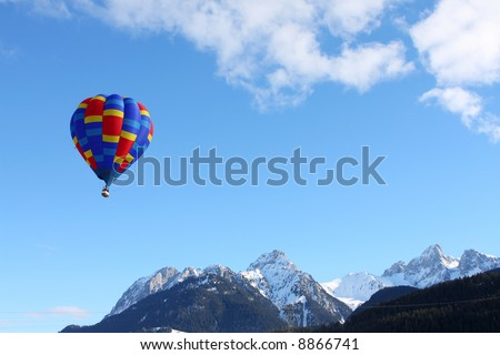 Colorful hot air balloon flying against a blue sky background - stock photo